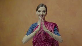 Pretty woman with hands joined in namaste greeting. Beautiful young female in ethnic hindu sari with bindi point on forehead joining hands in namaste greeting stock video footage