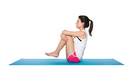 Beautiful young female exercising on a blue matt. Young female doing workout and exercising on a blue matt. Isolated on white royalty free stock image