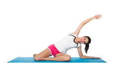 Beautiful young female exercising on a blue matt. Young female doing workout and exercising on a blue matt. Isolated on white stock photos