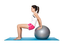 Beautiful young female exercising on a blue matt. Young female doing workout and exercising on a blue matt. Isolated on white stock images