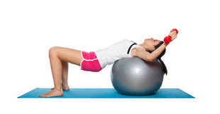 Beautiful young female exercising on a blue matt. Young female doing workout and exercising on a blue matt. Isolated on white stock photography