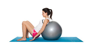 Beautiful young female exercising on a blue matt. Young female doing workout and exercising on a blue matt. Isolated on white royalty free stock photos