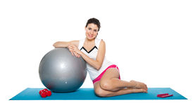 Beautiful young female exercising on a blue matt. Young female doing workout and exercising on a blue matt. Isolated on white stock image