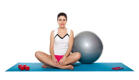 Beautiful young female exercising on a blue matt. Young female doing workout and exercising on a blue matt. Isolated on white royalty free stock images