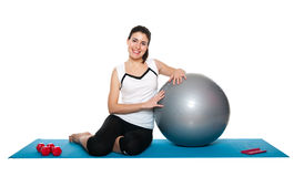 Beautiful young female exercising on a blue matt Stock Photography