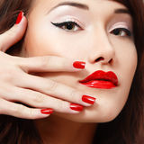 Beautiful young female face with vivid red lipstick and nail pol Stock Photo