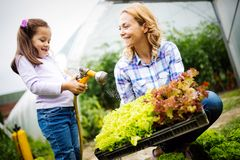 Beautiful young woman working in garden with her daughter stock photos