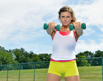 Beautiful young female fitness model (lifting) Royalty Free Stock Image