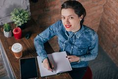 Beautiful young female freelancer with notepad and tablet have a coffee break. In loft interior room Stock Photo