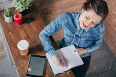Beautiful young female freelancer with notepad and tablet have a coffee break. In loft interior room Royalty Free Stock Photography