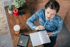 Beautiful young female freelancer with notepad and tablet have a coffee break. In loft interior room Stock Images