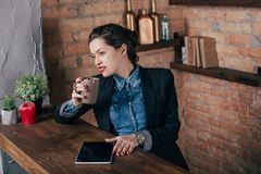 Beautiful young female freelancer with notepad and tablet have a coffee break. In loft interior room Stock Image