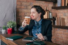 Beautiful young female freelancer with notepad and tablet have a coffee break. In loft interior room Stock Photography