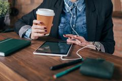 Beautiful young female freelancer with notepad and tablet have a coffee break. In loft interior room Stock Photos