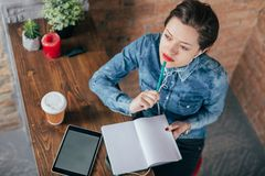 Beautiful young female freelancer with notepad and tablet have a coffee break. In loft interior room Royalty Free Stock Photo