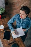 Beautiful young female freelancer with notepad and tablet have a coffee break. In loft interior room Royalty Free Stock Photos
