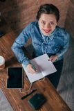 Beautiful young female freelancer with notepad and tablet have a coffee break. In loft interior room Royalty Free Stock Images