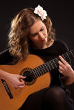 Beautiful young female guitar player. Against black background Royalty Free Stock Photography
