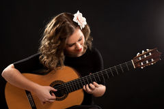 Beautiful young female guitar player. Against black background Royalty Free Stock Image