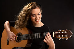 Beautiful young female guitar player. Against black background Royalty Free Stock Images