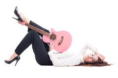 Beautiful young female guitarist lying down on white floor Stock Image