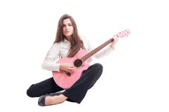 Beautiful young female guitarist sitting on white floor Stock Photo