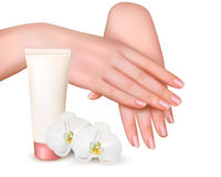 Beautiful young female hands with a cream and orchids. Stock Image