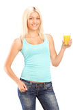 Beautiful young female holding a glass of orange juice and posin Royalty Free Stock Image