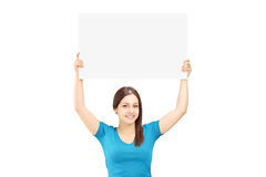 Beautiful young female holding a white panel above her head. Isolated on white background Royalty Free Stock Photo