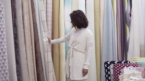 A beautiful young female among the huge variety of fabrics in the store. She smiles, looks around, passing a hand. Touching the texture. Variety of colors. Slow stock video footage