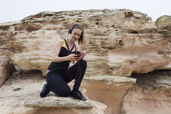 Beautiful young female jogger enjoying rest after workout while chatting on her mobile phone sitting on stone rock. Attractive fitness woman choosing song in royalty free stock photo