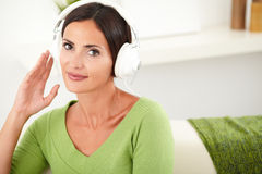 Beautiful young female listening to music. Portrait of a beautiful young female listening to music on headphones while sitting indoors Stock Image