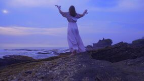 Beautiful young female in a long dress stands on the rocks on the ocean beach on Bali on the sunset with wonderful view stock footage
