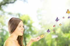 Beautiful young female with many colorful butterflies on her han Stock Image