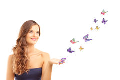 Beautiful young female with many colorful butterflies Stock Photography