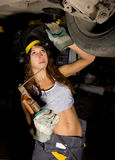 Beautiful young female mechanic inspecting car in auto repair shop. Girl welder is prepared to connect parts. Sexy Royalty Free Stock Image