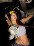 Beautiful young female mechanic inspecting car in auto repair shop. Girl welder is prepared to connect parts. Sexy Stock Images