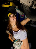 Beautiful young female mechanic inspecting car in auto repair shop. Girl welder is prepared to connect parts. Sexy. Mechanic Stock Images