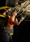 Beautiful young female mechanic inspecting car in auto repair shop. mechanic Royalty Free Stock Photography