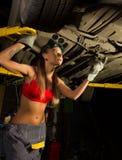 Beautiful young female mechanic inspecting car in auto repair shop. Sexy mechanic Stock Photo