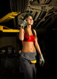 Beautiful young female mechanic inspecting car in auto repair shop. Sexy mechanic Royalty Free Stock Photo