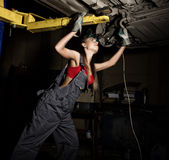 Beautiful young female mechanic inspecting car in auto repair shop. Sexy mechanic Royalty Free Stock Images