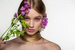 Beautiful young female model with blue eyes, perfect skin with flowers on the shoulder, her neck is wrapped in hair stock photography