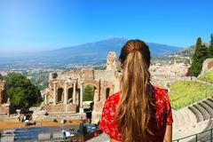 Beautiful young female model in the ruins of the ancient Greek theater in Taormina with the Etna volcano on the background, Sicily. Italy stock photography