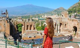 Beautiful young female model in the ruins of the ancient Greek theater in Taormina with the Etna volcano on the background, Sicily. Italy stock images