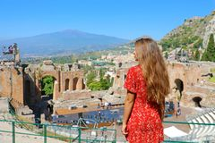 Beautiful young female model in the ruins of the ancient Greek theater in Taormina with the Etna volcano on the background, Sicily. Italy royalty free stock photo