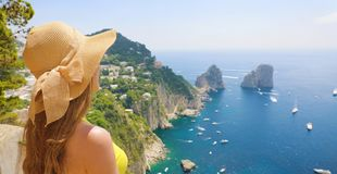 Beautiful young female model with straw hat in Capri Island with Faraglioni sea stack and blue sea water on the background, Capri stock photo