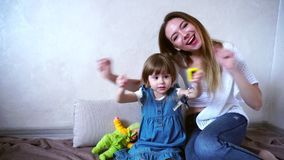 Beautiful young female mother and baby daughter posing at camera and laughing, sitting on floor in bright room in. Lovely women, young caring mother and daughter stock video footage