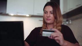 Beautiful young female online banking using a mobile computer and a credit card having a good mood. Beautiful young woman with long dark hair online banking stock video