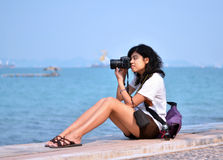 Young female photographer taking pictures on beach Stock Photos